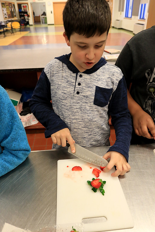 . Kids at the Boys and Girls Club of Fitchburg And Leominster participated in a cooking class on Wednesday, February 14, 2019. They learned to make pancakes and a topping of strawberries and blueberries. They heated them up to make a sort of jam for a topping. They where trying to be healthier then butter and syrup.  Aaron Trainque, 10, cuts up the strawberries during the class. SENTINEL & ENTERPRISE/JOHN LOVE