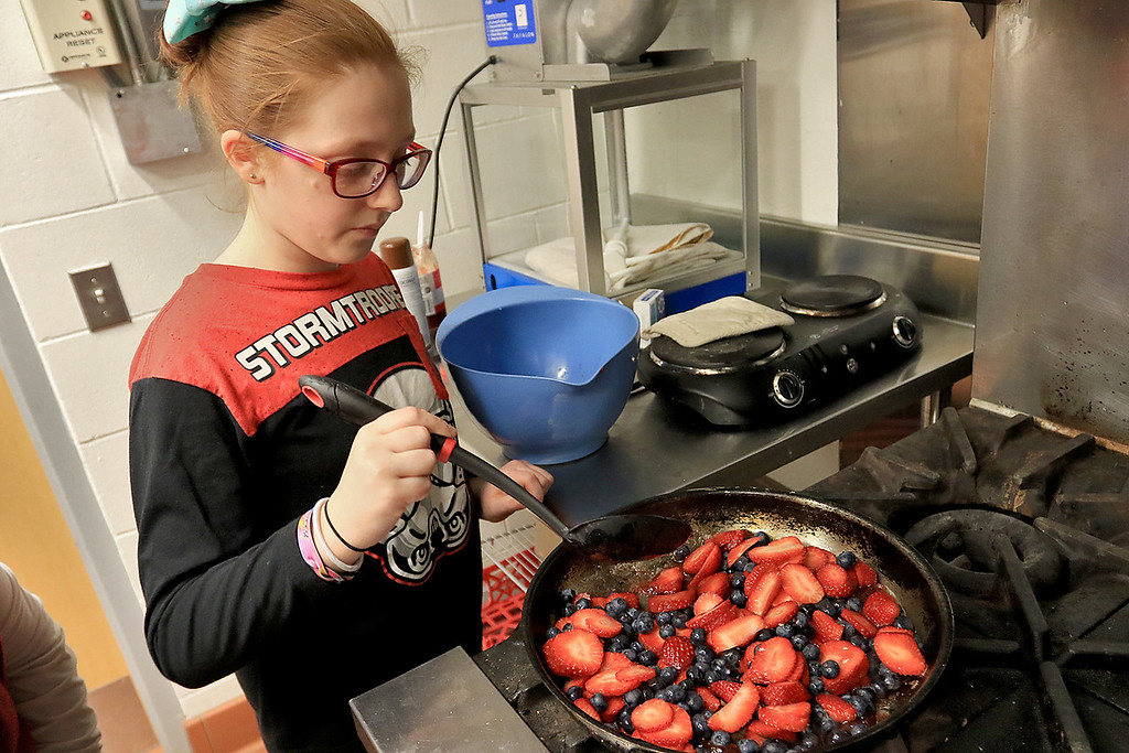 . Kids at the Boys and Girls Club of Fitchburg And Leominster participated in a cooking class on Wednesday, February 14, 2019. They learned to make pancakes and a topping of strawberries and blueberries. They heated them up to make a sort of jam for a topping. They where trying to be healthier then butter and syrup. Adalie Boisselle, 10, heats up the strawberries and blueberries for the topping.  SENTINEL & ENTERPRISE/JOHN LOVE
