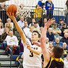 Record-Eagle/Brett A. Sommers Glen Lake's Xander Okerlund (3) converts a layup over Iron Mountain's Foster Wonders (00) during Tuesday's Class C boys basketball quarterfinal at Petoskey High School. Glen Lake won 66-49.