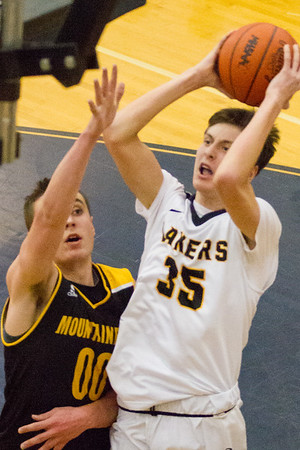 Record-Eagle/Brett A. Sommers Glen Lake's Reece Hazelton (35) shoots over Iron Mountain's Foster Wonders (00) during Tuesday's Class C boys basketball quarterfinal at Petoskey High School. Glen Lake won 66-49.