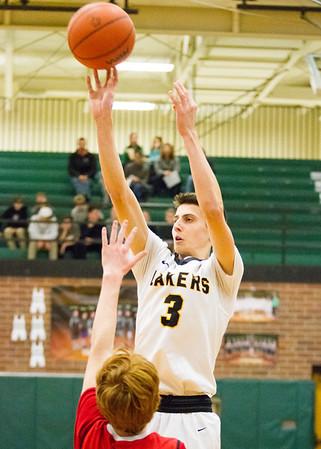 Record-Eagle/Brett A. Sommers Glen Lake's Xander Okerlund shoots over Whittemore Prescott's Tanner Harrison during Wendesday's regional championship boys basketball game at Houghton Lake High School. Glen Lake won 75-46.