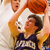 Record-Eagle/Brett A. Sommers Traverse City St. Francis' Danny Passinault drives agaisnt Glen Lake's Reece Hazelton during the first half of Friday's district championship game. Glen Lake won 61-33.