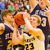Record-Eagle/Brett A. Sommers Glen Lake's Cade Peterson drives to the basket against Traverse City St. Francis' Keaton Peck, left, and Rob Dohm, right, during Friday's boys basketball district championship. Glen Lake won 61-33.
