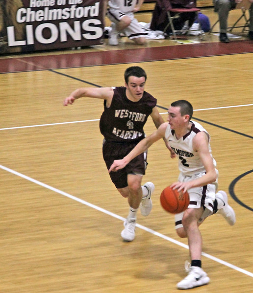 Chelmsford's #2-Christopher McCarthy brings the ball up court past Westford player #4-Scott Beattie. SUN/David H. Brow