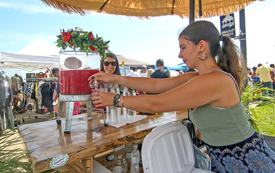 Emily Smith, co-owner of Straight-Up Coconut, serving a customer watermelon juice. The 2019 Lobster Fest in Bradley Beach, NJ on 8/31/19. [DANIELLA HEMINGHAUS]