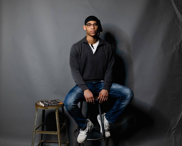 Bradley Richards, a sophomore in economics and  pre-law, poses on a stool while telling the story of what inspires him to write and share his poetry. Richards said he is inspired by a book named The New Jim Crow by Michelle Alexander. (Olivia Bergmeier | Collegian Media Group)