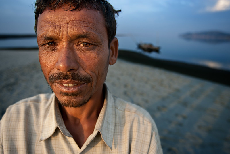Fisherman from Bangladesh with his boat. Near Tezpur. Assam.