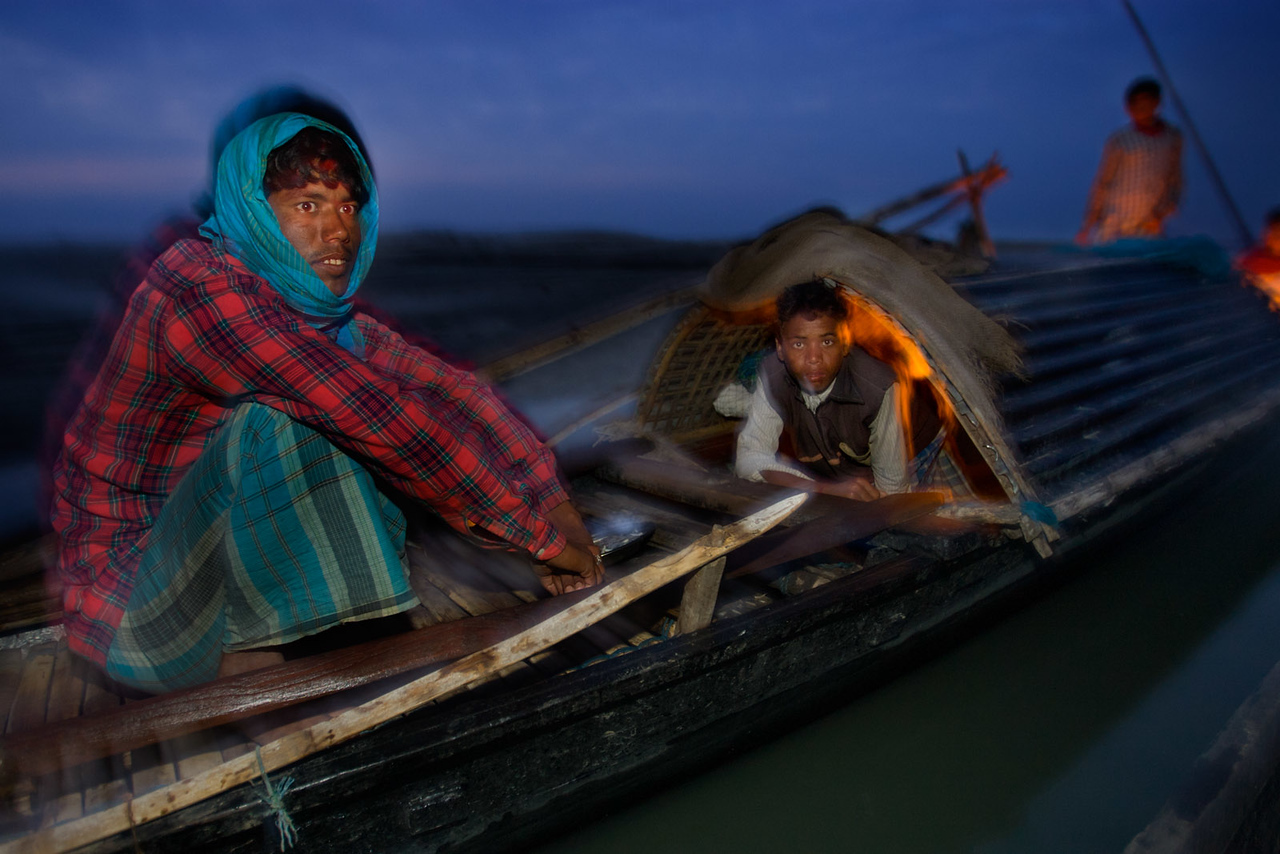 Fishermen from Bangladesh preparing food on their boat. Near Tezpur. Assam.