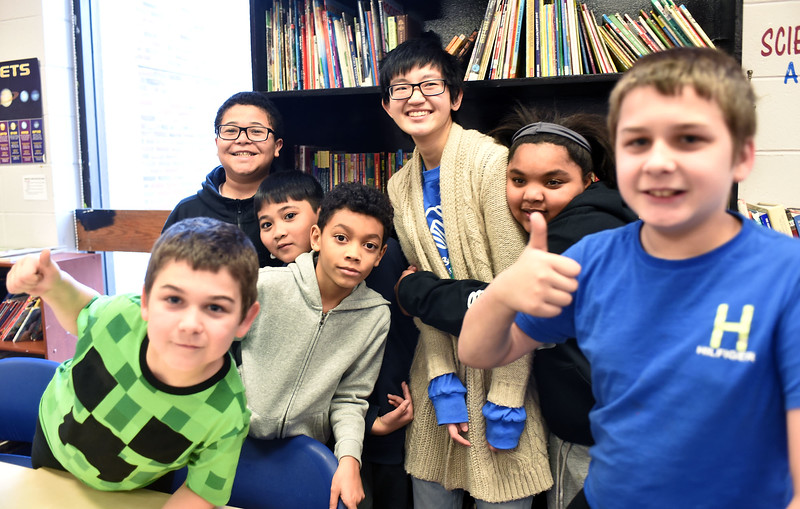 Volunteer Andy Lu 20, middle standing with some of the kids he works with in the Brain Center in the Boys & Girls Club, L-R, Kyle Page 9, Aliel Torres 10, Danny Long 10, Royce Herrera 8, Andy Lu, Olivia Musing 12, and Christian Page 11. SUN/ David H. Brow