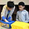 Volunteer Andy Lu 20, works with Royce Herrera 8, on a lego project in the Brain Center at the Boys & Girls Club in Lowell. SUN/ David H. Brow