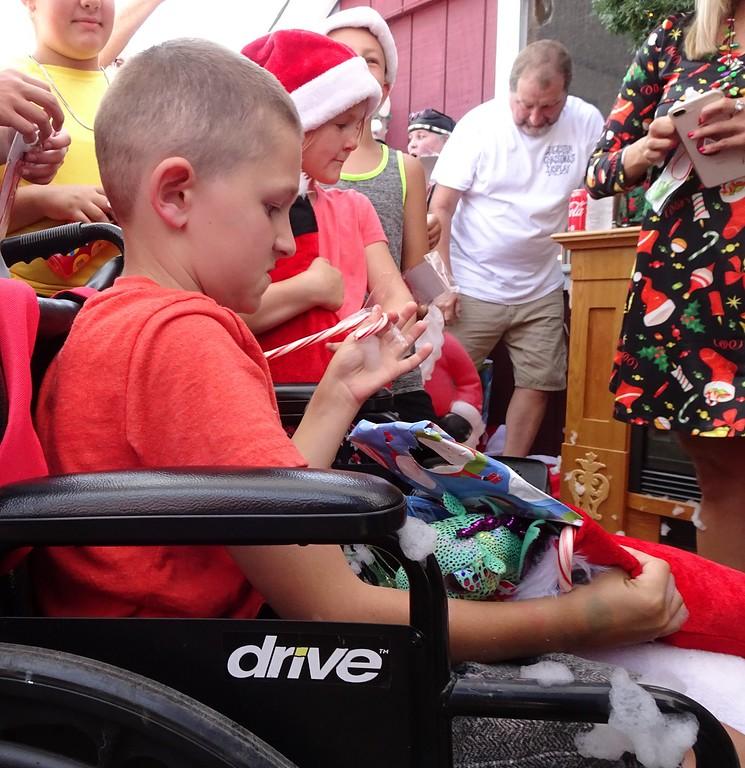 . Brandon Cotoni opens a gift from Santa Claus. SENTINEL & ENTERPRISE/ NICK MALLARD