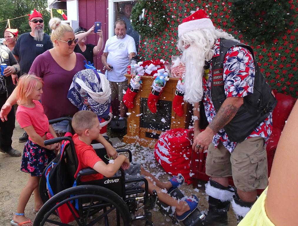 . From left, Kaylee Cotoni, Jennifer Cotoni and Brandon Cotoni say hello to Santa Claus. SENTINEL & ENTERPRISE/NICK MALLARD