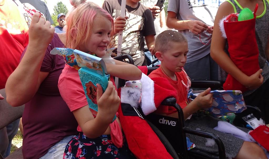 . Kaylee Cotoni, 7, and Brandon Cotoni, 8, open gifts from Santa. SENTINEL & ENTERPRISE/NICK MALLARD