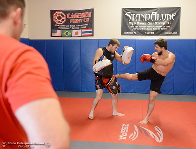 StandAlone Owner Jason Pietz at left watches as Brandon Ricetti of Chico, at right gets in some pad work with Ryan Hamilton at left as he trains at StandAlone Mixed Martial Arts in Chico, Calif. Wed. Aug. 8,  2018.  (Bill Husa -- Enterprise-Record)