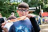 "KELLY FLETCHER, REFORMER CORRESPONDENT -- Anthony Doell savors an order of glazed bacon on a stick from ""Bacon Me. Crazy"" at Baconfest on. Saturday at Kampfires Campground"