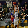 KRISTOPHER RADDER - BRATTLEBORO REFORMER<br /> Brattleboro's Calvin Lafland takes a jump shot while being covered by Spaulding's Hamisi Wabuti during a Division 1 boys varsity basketball playoff game at Brattleboro Union High School on Wednesday, March 1, 2017.