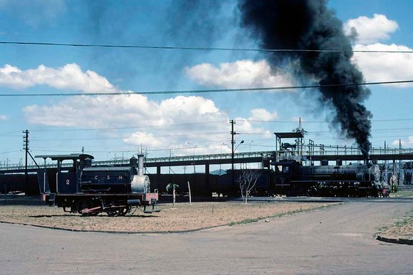 Capivari power station No 5, near Tubarao, Brazil, 21 October 1976.  The Jung 2-8-2 (11944 / 1954) leads a coal train past preserved 0-4-0ST No 2 (Manning Wardle 375 / 1871).  The 2-8-2 was also subsequently preserved.  Photo by Les Tindall.
