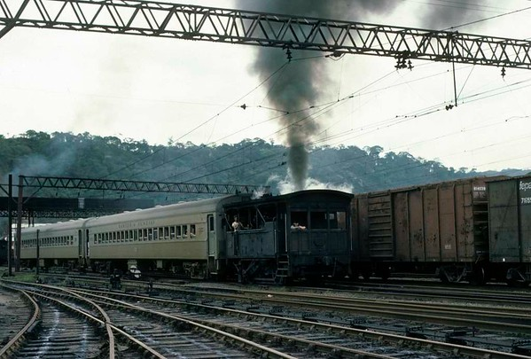 Paranapiacaba station, Santos a Jundiai Railway, Brazil, 18 October 1976.  Another of the 0-4-0 tram engines departs for Santos with half an EMU.  The other two EMU coaches with pantographs and motors are left in the station until two more coaches are brought up the incline from Santos.   Photo by Les Tindall.