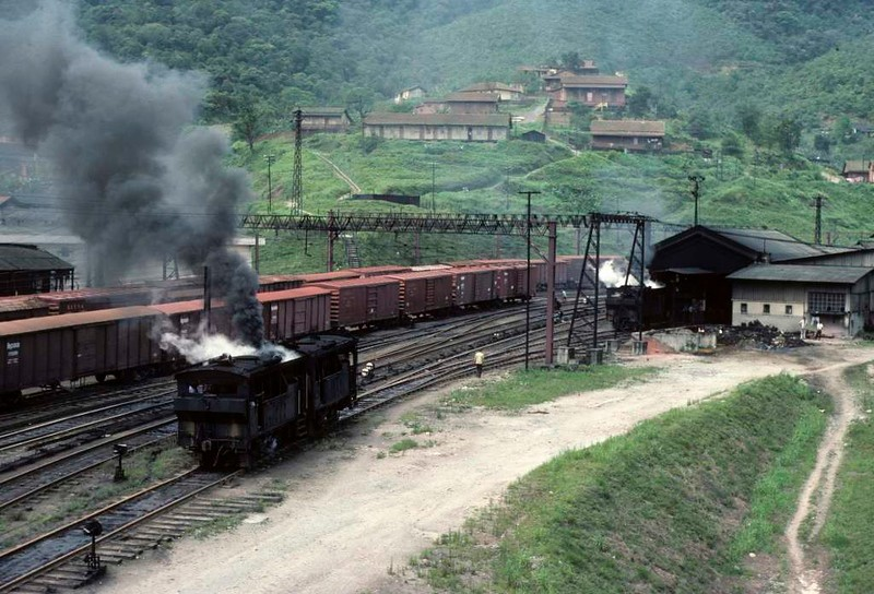 Paranapiacaba station, Santos a Jundiai Railway, Brazil, 18 October 1976.  Two tram engines go on shed past sidings full of wagons waiting to go down the inclines.   Photo by Les Tindall.