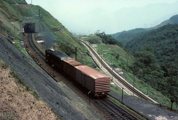 Paranapiacaba, Santos a Jundiai Railway, Brazil, 18 October 1976.  Another of the 0-4-0 tram engines propels a coach and two wagons up one of the inclines.  The then new Japanese-built electric rack railway is below.   Photo by Les Tindall.