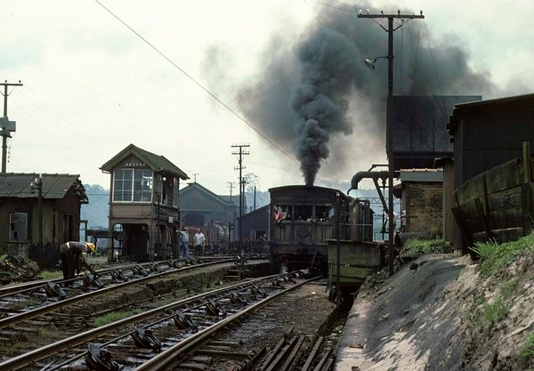 Paranapiacaba station, Santos a Jundiai Railway, Brazil, 18 October 1976.  No 15, built by Robert Stephenson in 1902, takes water at the summit of the top incline before taking two wagons down to Santos.  Locals, possibly the families of railway staff, ride on the footplate at the front of the engine.  Photo by Les Tindall.