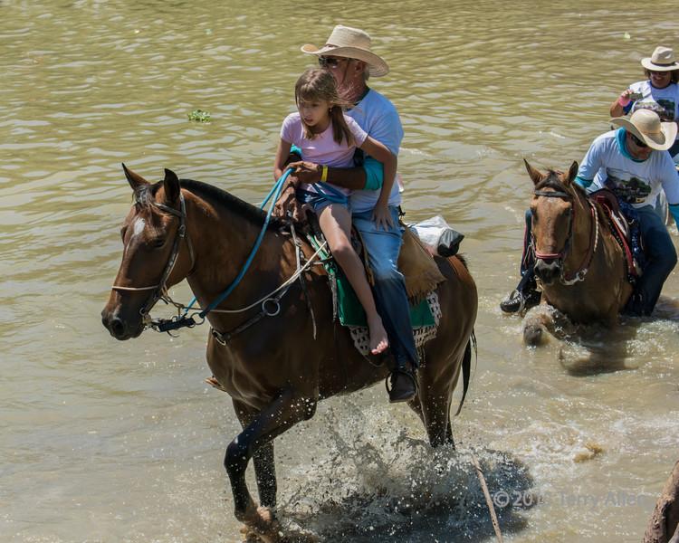 Horseman-and-daughter-crossing-the-Pixaim-River-on-horseback,-Pantanal,-Brazil