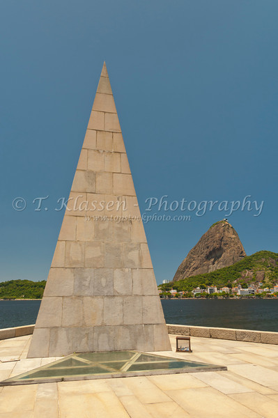 An obelisk shaped monument to the founder of the city of Rio De Janeiro Estacio de Sa with Sugarloaf in the background.