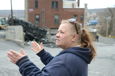 Lori Knopp of Mount Carmel talks about the minivan she recently bought and had dropped off for service at Greco's Service in Mount Carmel only to have a dump truck loaded with coal land on it on Wednesday morning.