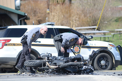 State Police officers look over a motorcycle accident that happened Thursday on Forrest Hill Road in front of the Green Ridge Market in Mifflinburg.