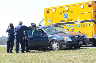 State Police and emergency personnel talk to a person inside a car involved in a accident with a motorcycle Thursday on Forrest Hill Road in front of Green Ridge Market in Mifflinburg.