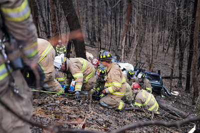 Firefighters carry up the driver of an SUV off of Mile HIll Road in Sunbury on Tuesday evening.