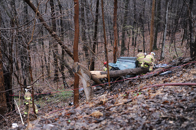 Firefighters cut the top off of an SUV that slid off of Mile Hill Road on Tuesday evening in Sunbury.