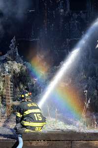 A fire fighter sprays water onto a home on White Deer Pike creating a rainbow in the process during a house fire on Thursday morning.