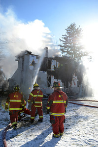 Fire fighters pour water onto a home on White Deer Pike Thursday morning while trying to extinguish the fire.