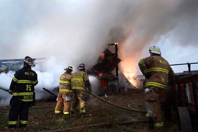 Fire fighters hose down a large barn fire on Route 54 just outside of Turbotville on Thursday evening.