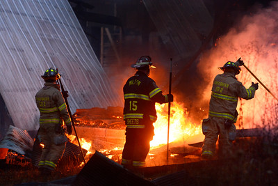 Fire fighters clear debris away from flames in a barn fire on Route 54 Thursday evening just outside of Turbotville.