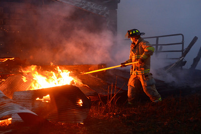 A fire fighter moves debris away from flames at a barn fire on Route 54 outside Turbotville on Thursday evening.