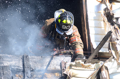 A firefighter sticks his head out of a opening in the second story of a home on Creek Road in Beaver Township while batteling a fire on Monday afternoon.