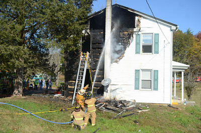 Firefighters spray water onto a home along Creek Road in Beaver Township after it caught fire on Monday afternoon.