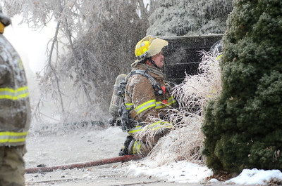A fire fighter holds a hose in place despite being covered in ice while fighting a fire in Danville on Tuesday on Ash Street.