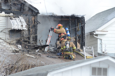 Fire fighters stand on a back porch roof of a home on Ash Street in Danville while trying to extinguish a house fire on Tuesday.