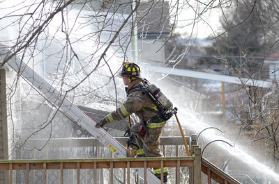 A fire fighter climbs a ladder in slick conditions while trying to extinguish a house fire on Ash Street in Danville on Tuesday.