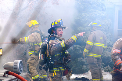 A fire fighter shouts directions during a house fire on Tuesday on Ash Street in Danville.