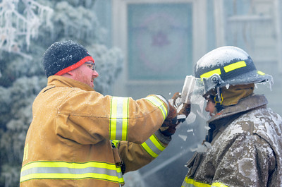 Fire fighters help keep the ice off of one another at a house fire in Danville on Tuesday.