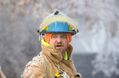 Icicles hang off of the helmet of a fire fighter helping to put out a house fire on Tuesday in Danville on Ash Street.