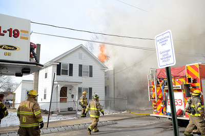 Flames shoot out the roof of a home on Ash Street in Danville on Tuesday.