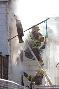 Fire fighters spray water on a Spruce Street home in Danville on Thursday afternoon after it caught on fire.
