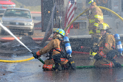Fire fighters spray water onto a home at 109 Spruce Street in Danville during a fire on Thursday afternoon.