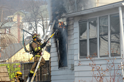 A fire fighter pulls away siding to get at flames in the side of a home on Spruce Street in Danville on Thursday afternoon.