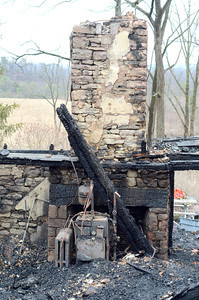 A furnace sits in front of a fire place in a house at 60 S. Smith Road in Rush Township that burnt down early Friday morning killing three children that lived in the home.